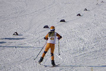 the girl in a yellow suit runs along the ski .