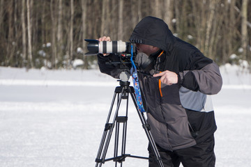 videographer working in the snow in summer mountain .