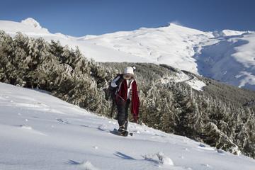 Mujer joven disffrutando de la nieve en la montaña