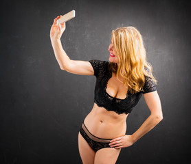 Woman in sexy lingerie taking selfie photo with mobile phone