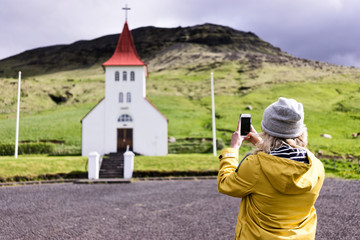 Woman taking a picture on her phone of an Icelandic church