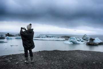 Woman taking a picture of icebergs her phone