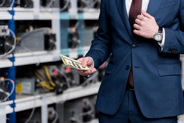 cropped view of businessman holding cash at ethereum mining farm