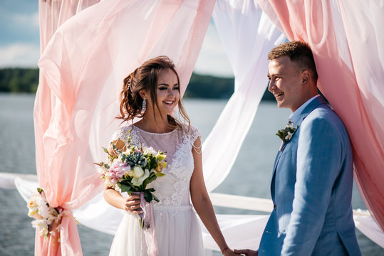 A beautiful and happy couple, the bride and groom, stand on the pier under the wedding arch