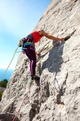 Girl climbs the rock.