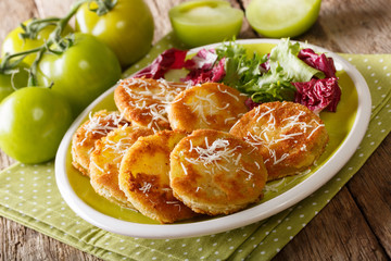 simple snack of fried green tomatoes with fresh lettuce close-up on a plate. horizontal Wall mural