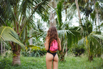 rear view of slim girl with backpack posing on tropical resort with palm trees Wall mural