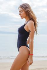 side view of beautiful slim girl posing in swimsuit near the ocean