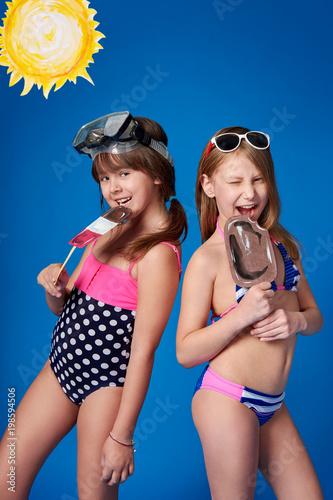 f6aa02dea2cd4 Beautiful two children girlfriend in swimwear smiling,eating ice cream.Young  cheerful girls advertise