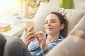 Woman on the couch using a smartphone