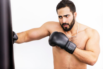 Muscular handsome topless boxer wears black gloves fights before white background