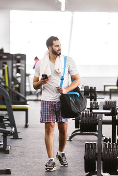 Muscular man walking in the gym holding bag and phone
