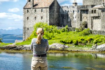 Beautiful lady looking at Eilean Donan Castle during a warm summer day - Dornie, Scotland