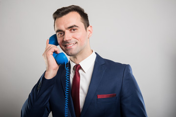 Attractive business man talking at blue telephone receiver