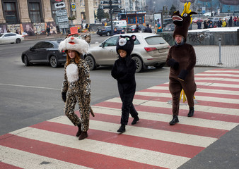 Women dressed as cats and a man dressed as a deer, who pose for pictures with tourists, walk on a pedestrian crossing, in central Kiev