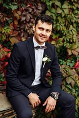 Handsome man wearing informal dress sitting in the park ivy wall background