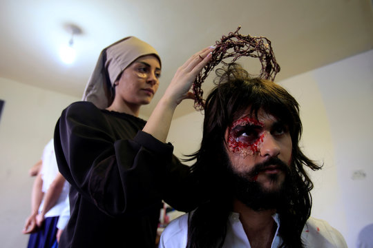 A Christian woman holds a crown of thorns during a reenactment of the crucifixion of Jesus Christ on Good Friday in al-Qraya village