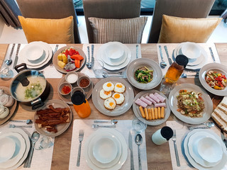 breakfast on table served with  foods,boiled rice,fried egg,sausage,bread,pastries,hot and cold drink,coffee.