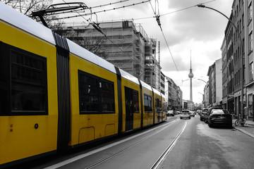 gele Straßenbahn in Berlin vor schwarz weißem Hintergrund