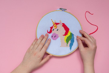 Embroidery of a unicorn on a pink background with a cross in a frame, a trend of 2018, a concept of surrealism and fantasy in the style of pop art