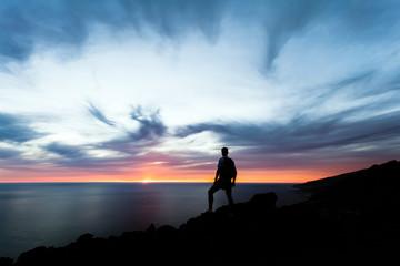 Celebrating or meditating man looking at sunset ocean