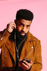 Cool n with beard holding his cell phone and  touching headphone in ear, isolated on pink studio background