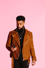 Cool African American man with beard looking down at his phone surprised, isolated on pink studio background