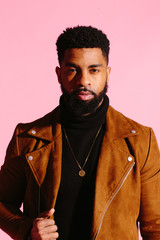 Simple portrait of a cool African American man with beard, isolated on pink studio background