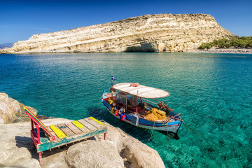 Clear sea and boat at Matala resort. Crete, Greece