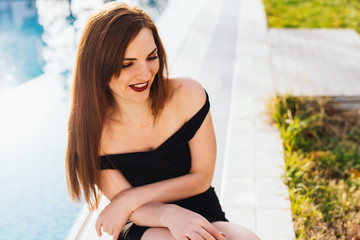 happy long-haired young woman in a black dress is sitting by the blue pool, laughing in the sun