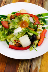 Pickled mushroom salad with raw fresh vegetables. Decorated with dill and slices of red sweet pepper. Vertical.