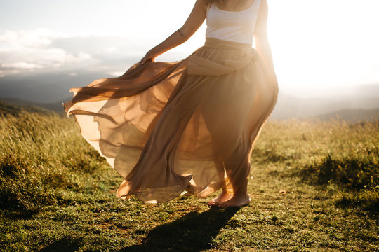 woman wearing a long skirt blowing in the wind in the summer sun
