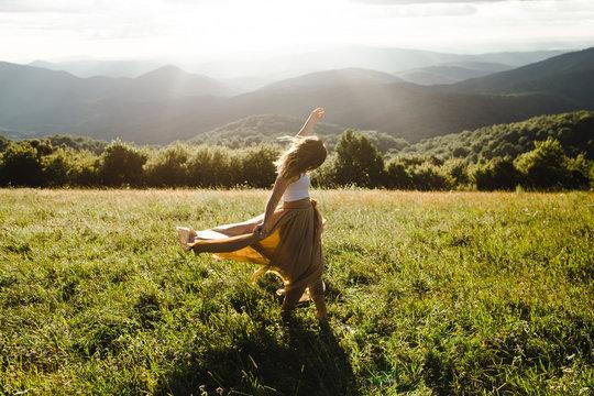 Woman wearing long dress spinning in a field in the summer sun