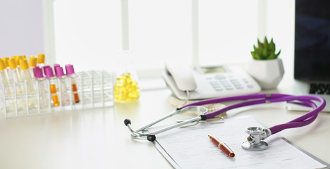 closeup of the desk of a doctors office with a stethoscope in the foreground and a bottle with pills in the background