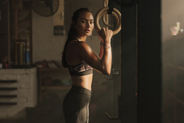 Woman holding gymnast rings at the gym