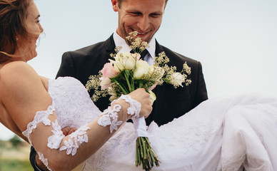 Happy groom carrying beautiful bride
