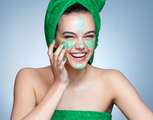 Laughing girl applying moisturizing cream on her face. Photo of young girl in green towels with flawless skin on blue background. Skin care and beauty concept