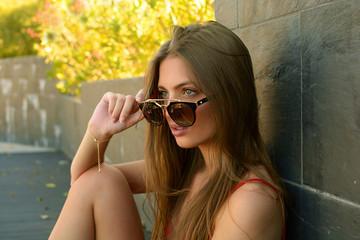 Chica joven con pelo largo observando por encima de las gafas