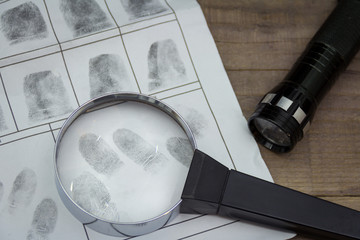 Fingerprints on paper with a magnifying glass. Flashlight in the background