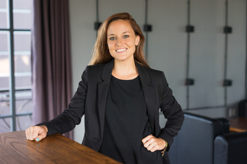 Closeup portrait of smiling young beautiful brown-haired woman looking at camera and standing at reception desk in hotel. Beautiful business woman concept. Front view.