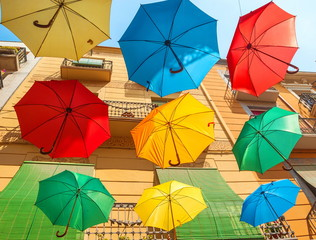 Multicolored umbrellas in the sky above the city