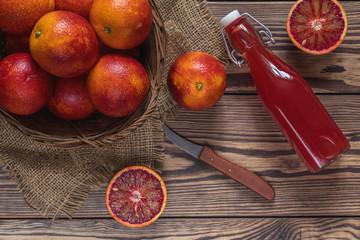 Blood orange fruit in a wicker basket and bottle juice on dark wooden table.