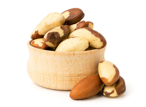 Brazilian nuts in wooden plate, closeup.