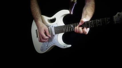 A man is playing on a white electric guitar on a black background - 2.