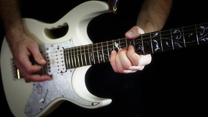 A man plays solo on a white electric guitar on a black background - 4.