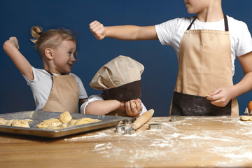 Two schoolboys brothers having fight in kitchen while cooking together. Furious blonde little boy threatening his unrecognizable brother while quarreling, baking cookies in kitchen. Cropped shot