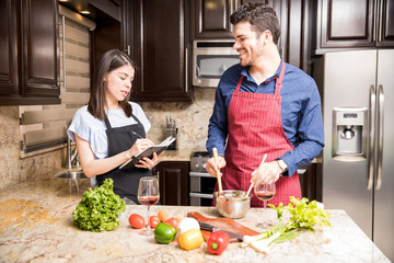Couple preparing food from recipe book at home