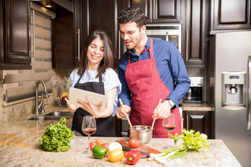 Latin couple using digital tablet in the kitchen for cooking