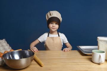 Picture of determined excited little boy wearing chef uniform standing at kitchen table with metal bowl, rolling pin, tray, flour and eggs, ready to start making dough for pancakes. Food and nutrition
