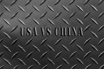 Words USA vs China written on textured steel sheet with diamond plate pattern/USA and China steel tariff dispute concept